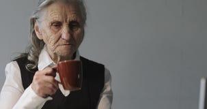 Een oude vrouw drinkt koffie en werkt achter laptop in het bureau stock video
