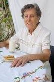 Een oude vrouw heeft haar ontbijt stock afbeeldingen