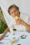 Een oude vrouw heeft haar ontbijt stock foto