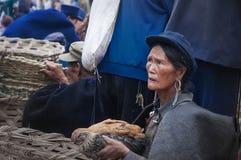 Een oude vrouw het verkopen kip Stock Foto's