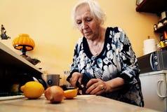 Een oude vrouw kookt stock foto's