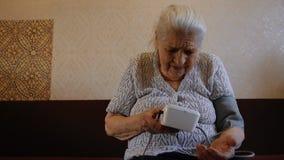 Een oude vrouw meet haar bloeddruk Oma ` die s een tonometer met behulp van stock video