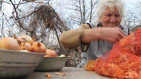 Een oude vrouw met grijs haar neemt uien op alvorens in de keuken, organische groenten, haar eigen gewas te koken stock video