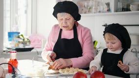 Een oude vrouw met een klein meisje die desserts in de keuken maken Een oude vrouw die een appel snijden stock footage