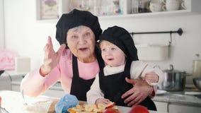 Een oude vrouw met een kleine meisjes golvende handen en het kijken in de camera in de keuken stock video