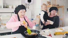Een oude vrouw pannekoeken in de heldere keuken maken en een andere oude vrouw die een klein meisje op haar handen houden stock videobeelden