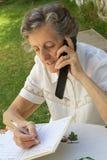 Een oude vrouw spreekt op mobiele telefoon en neemt sommige nota's in haar agenda Stock Foto's