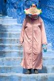 Een oude vrouw wandelt door de straten van Chefchaouen, de blauwe stad in Marokko, met haar traditioneel kostuum stock fotografie