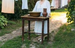 Een oude vrouw in wit bevindt zich dichtbij een lijst waarop leugenprinadzheshnosti voor was Hangend kleren en linnen, droogt het royalty-vrije stock afbeelding