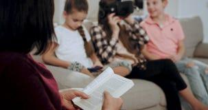 Een oude vrouwenoma die een boek op de bank lezen terwijl haar kleinkinderen die in een virtuele werkelijkheidsglazen hebben zij  stock footage