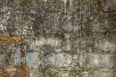 Een oude vuile concrete muur met uitpuilende rode bakstenen Ongelijke ruwe oppervlakte vlekken van cement en verf royalty-vrije stock foto