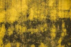 Een oude vuile gele concrete muur met barsten en zwarte vlekken van verf en vorm Ruwe Oppervlaktetextuur stock afbeeldingen