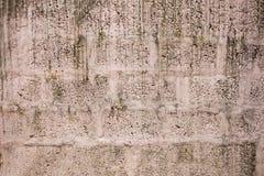 Een Oude witte roze concrete muur van grote bakstenen druppels van vuil en verf Ruwe muuroppervlakte stock afbeelding