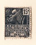 Een oude zwarte Franse postzegel met een illustratie van een gestileerde Afrikaanse vrouw die een koloniale tentoonstelling in 19 royalty-vrije stock afbeelding