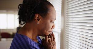 Een ouder zwarte mournfully kijkt uit haar venster stock afbeelding