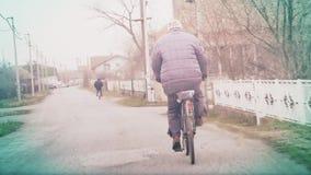 Een oudere mens berijdt een fiets stock video