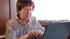 Een oudere vrouw controleert de berichten thuis op sociale netwerken op laptop Zij zit bij de lijst stock videobeelden