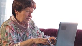 Een oudere vrouw controleert de berichten thuis op sociale netwerken op laptop Zij zit bij de lijst stock video