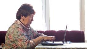 Een oudere vrouw controleert de berichten thuis op sociale netwerken op laptop Zij zit bij de lijst stock footage