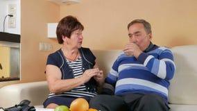 Een oudere vrouw geeft een pil thuis met een glas water aan haar echtgenoot op de laag Slecht man welzijn taking stock videobeelden