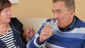 Een oudere vrouw geeft een pil thuis met een glas water aan haar echtgenoot op de laag Slecht man welzijn taking stock footage