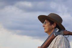 Een oudere vrouw met haar geweer let op de zonsondergang royalty-vrije stock afbeelding
