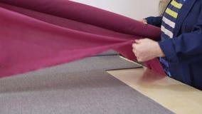 Een oudere vrouw in een meubilairfabriek neemt roze materiaal voor het naaien op stock video