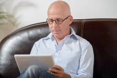 Een oudste bekijkt een digitale tablet Royalty-vrije Stock Foto