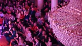 Een overleg in de concertzaal met een grote kristalkroonluchter Mensen die op de stoelen zitten en hun handen slaan stock videobeelden