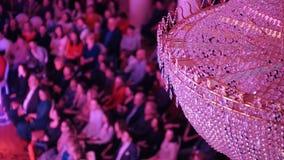 Een overleg in de concertzaal met een grote kristalkroonluchter Mensen die op de stoelen zitten stock video