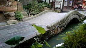 Een overspannen steenbrug over de rivier, een bluestonebrug Stock Foto