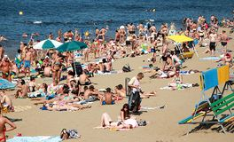 Een overvol de zomerstrand, mensen zonnebaadt in de zon en zwemt in zeevaart-binnenvaart, oceaan stock fotografie
