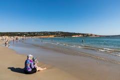 Een overvol strand in de zomer als mensen geniet van zwemmend en speel in de oceaan en het zand royalty-vrije stock afbeeldingen