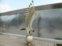 Een overzees adelaarslicht tegen een metaal weerspiegelende barrière Stock Foto