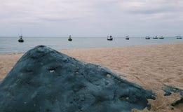 Een overzeese landschapsmening met vissersboten en reuzerots op het zandstrand stock afbeeldingen