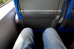 Een paar benen gekleed in jeansreizen door trein stock foto