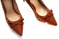 Een paar bruine gekleurde hoge dames hielt schoenen met een booglint bij de voorzijde stock fotografie