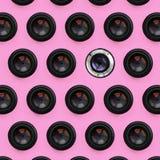 Een paar cameralenzen met een gesloten opening liggen op textuurachtergrond van roze de kleurendocument van de manierpastelkleur  royalty-vrije stock fotografie
