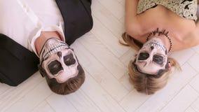 Een paar in Carnaval-kostuums ligt op de vloer op een witte vloer De partij van Halloween stock footage