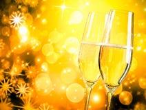 Een paar champagnefluiten met gouden bellen op gouden lichte achtergrond Stock Foto