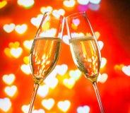 Een paar champagnefluiten met gouden bellen op harten bokeh achtergrond Stock Afbeeldingen