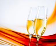 Een paar champagnefluiten met gouden bellen op onduidelijk beeld lichte achtergrond Stock Foto's