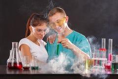 Een paar chemici, tribune in rook op een donkere achtergrond en onderzoekt een fles met een groene vloeistof Royalty-vrije Stock Afbeelding