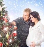 Een paar die de Kerstboom (zwangere vrouw) verfraaien Stock Foto's