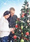 Een paar die de Kerstboom (zwangere vrouw) verfraaien Stock Fotografie