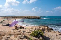 Een paar die in het mooie strand onder een purpere tent ontspannen stock foto