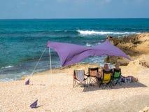 Een paar die in het mooie strand onder een purpere tent ontspannen stock foto's