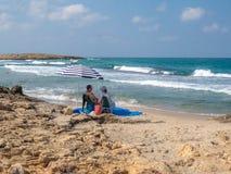 Een paar die in het mooie strand onder een purpere tent ontspannen royalty-vrije stock afbeelding