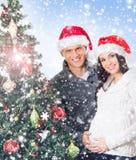 Een paar die op de baby bij Kerstmis dichtbij de boom wachten Royalty-vrije Stock Afbeeldingen