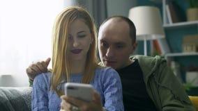Een paar die samen een smartphone op de bank in zijn woonkamer gebruiken stock videobeelden